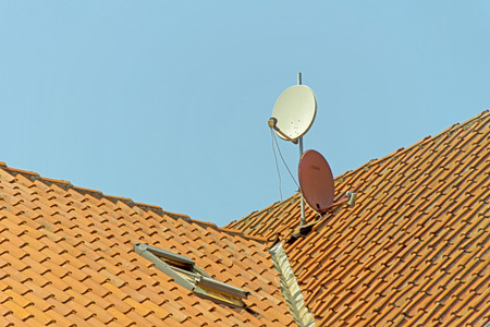 sky bachground: Satellite Dish - Two satellite dish on the roof of a house  Stock Photo