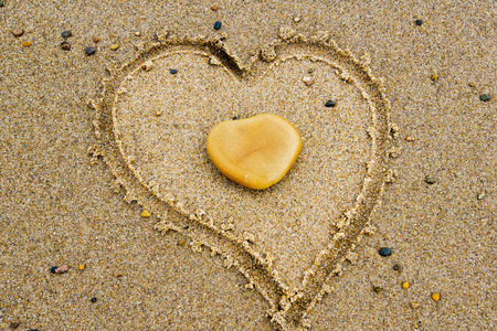 Heart on Heart - A stone heart and a heart in the sand on the beach at the Ocean  photo