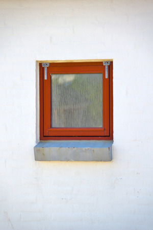 Window - A red window on a white wall.