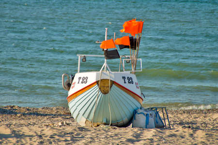 A fishing boat is lying on the beach at the coast of the north sea.