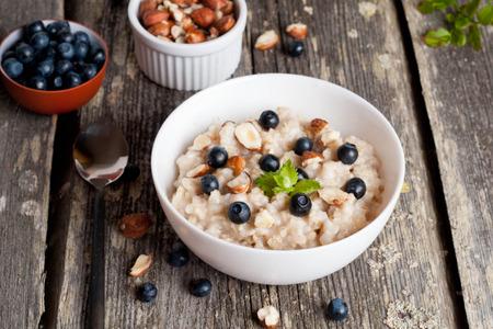 oatmeal bowl: Bowl of oatmeal porridge with blueberry, close up, horizontal