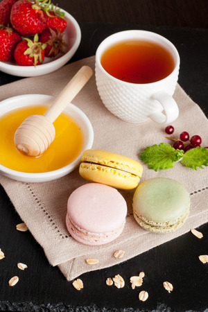 chocolate biscuit: Macarons with Cup of tea on black background, vertical Stock Photo