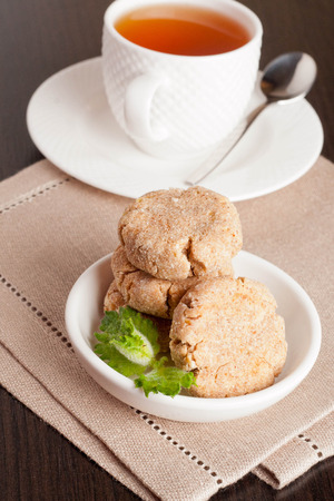 pista: Coconut butter cookies with cup of tea, vertical, close up