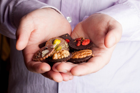 confect: Beautiful chocolate in palms, close up Stock Photo