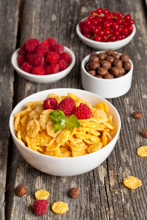 dry food: Cornflakes and different Berries, vertical, close up Stock Photo