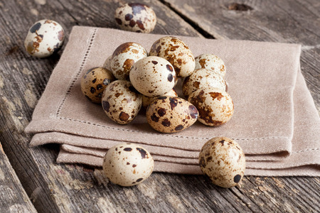 Quail eggs on rustic wooden table, horizontal, close up