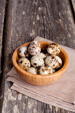 huevos codorniz: huevos de codorniz en la mesa de madera rústica, vertical, de cerca