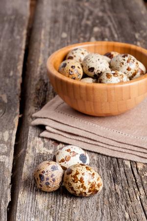 huevos de codorniz: huevos de codorniz en la mesa de madera rústica, vertical, de cerca