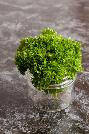 curly leafed: organic fresh bunch of parsley in a glass jar closeup, vertical