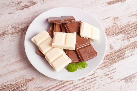 porous: Porous white chocolate and milk chocolate on a white wooden background, closeup, horizontal, top view Stock Photo