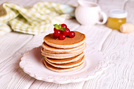 Stack of fluffy pancakes with berry on top, close up, horizontal