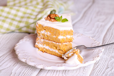 Close up of creamy sweet walnut carrot cake on a fork with white background. close up, horizontal