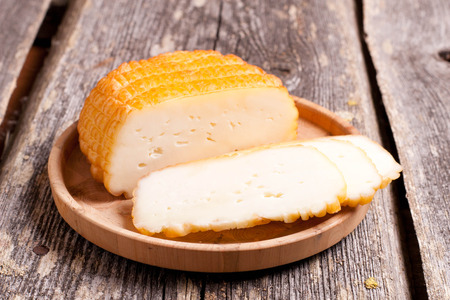 Home deliciouse smoked rustic cheese on old board. close up, horizontal Stock Photo