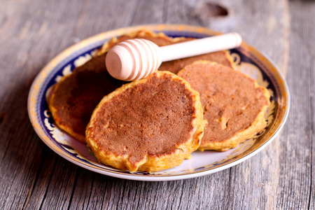 blini: pumpkin pancakes on a plate for breakfast with honey, horizontal, close up, top view