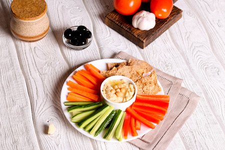 hummus served in a bowl with fresh vegetable sticks and whole grain crackers, horizontal, close up, top view