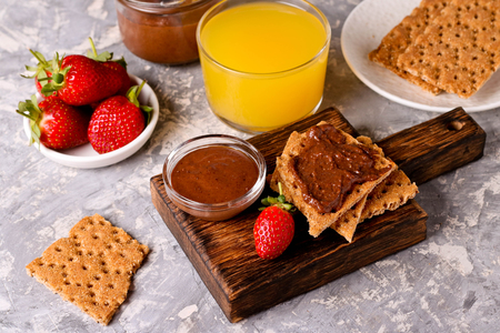 crackers spread with Chocolate Hazelnut Filling and Strawberries, with Small Bowls with Strawberries and Chocolate Paste nearby, close up, horizontal