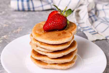 plato del buen comer: delicious healthy pancakes with strawberries on white plate, horizontal, close up