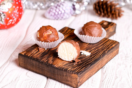 Handmade chocolate coconut candy on wooden table with Christmas and New Year decor. close up, horizontal Reklamní fotografie