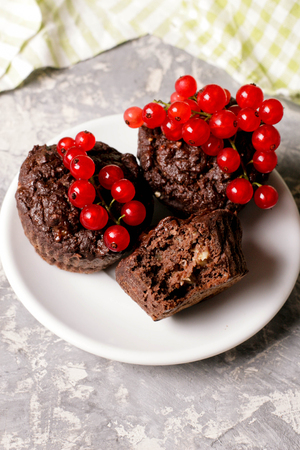 Chocolate muffin with redcurrant on white. healthy dessert, close up, vertical, top view Stock Photo