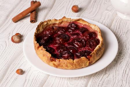 plum pie on a white plate, close up, horizontal