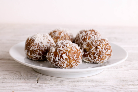 Homemade date candies covered with chocolate and shredded coconut, close up, horizontal Banco de Imagens