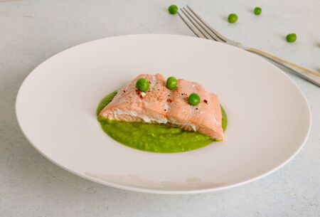 Baked salmon steak with sesame seeds and served with mashed green peas, close up, horizontal