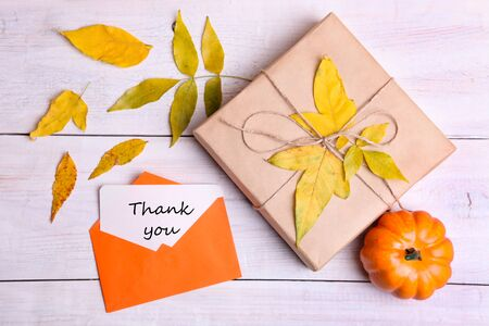 Gift and note in an envelope on wooden table. Concept autumn, autumn holiday. Stock Photo