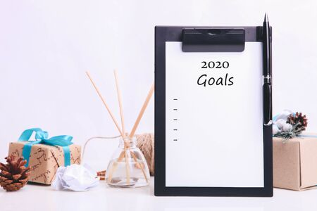 A list of New Year's goals and gifts on a neutral background.