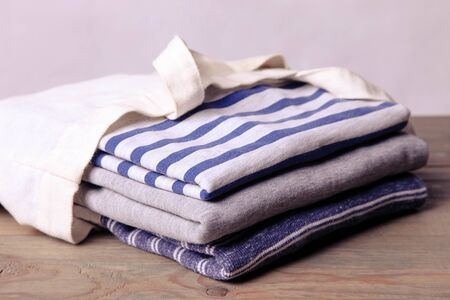A stack of sweatshirts in an eco bag on a neutral background. Purchase concept.