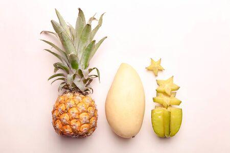 Frutas exóticas maduras sobre fondo beige. Foto de archivo
