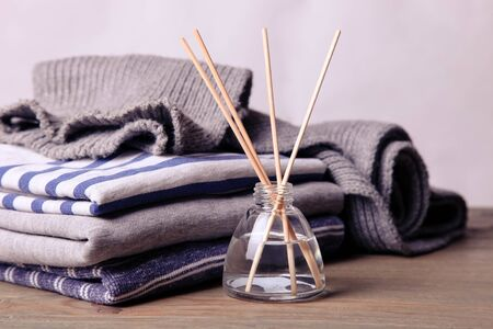 Reed freshener on a background of sweatshirts and a scarf on a neutral background. Air freshener concept.