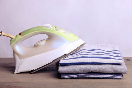 A stack of ironed sweatshirts and an iron on a neutral background. Foto de archivo