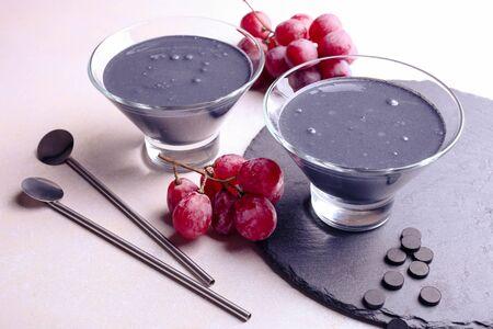 Yogur negro con carbón activado y uvas sobre un fondo blanco.