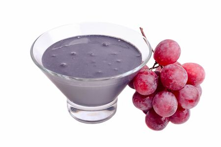 Black yogurt in a bowl with red grapes isolated on a white background.