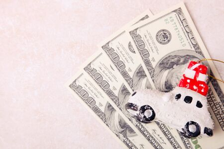 Toy car with gifts and money on a white background. Purchase concept.