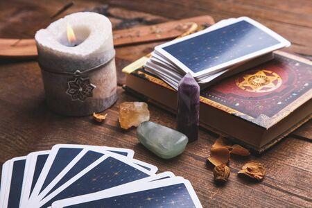 Wahrsagerei Tarotkarten und magisches Zubehör auf braunem Holzhintergrund. Okkultismus-Konzept.