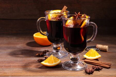 Red mulled wine with spices and corkscrew on a brown background. Stock Photo