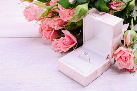 Pink roses with a ring in a gift box on a pink background.