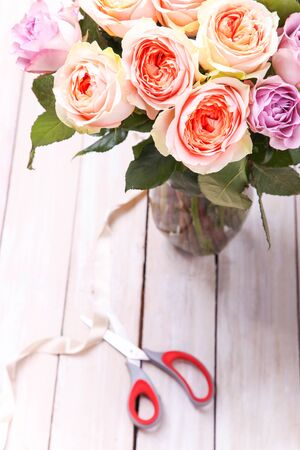 A bouquet of hybrid tea roses and floribunda in a vase on a white background. 免版税图像
