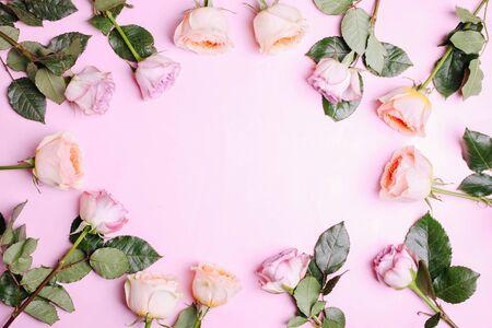 A bouquet of hybrid tea roses and floribunda on a pink background. 免版税图像
