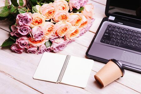 Laptop and bouquet of hybrid tea roses on a white background. Concept love online. 스톡 콘텐츠