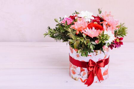 Bouquet of different flowers in a package on a white background. 스톡 콘텐츠