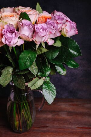 A bouquet of hybrid tea roses and floribunda in a vase on a black background.
