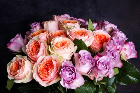 A bouquet of hybrid tea roses and floribunda on a black background.
