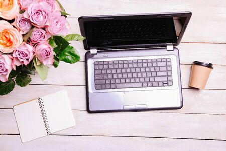 Laptop and bouquet of hybrid tea roses on a white background. Concept love online. 免版税图像