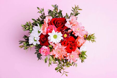 Bouquet of different flowers on a pink background.