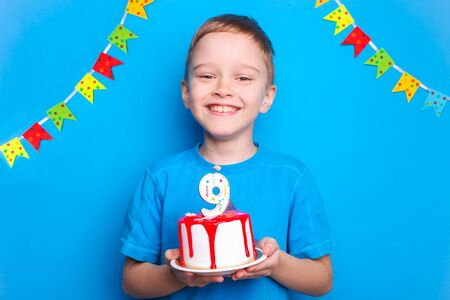 Happy boy holds a birthday cake on a blue background. Birthday concept.