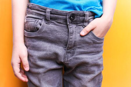 Boy in gray jeans close-up. Stylish look.