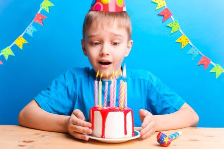 Happy boy in a festive cap blows out the candles on the cake on a blue background. Birthday concept.
