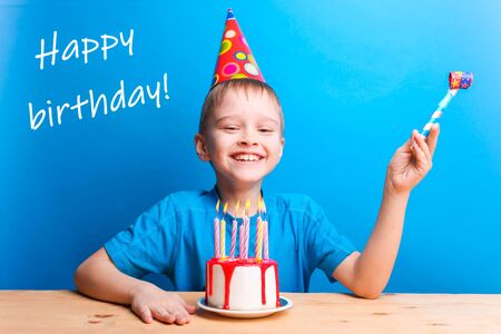 Happy boy in a festive cap and a pipe on a blue background. White cake with red icing and candles. Birthday concept.